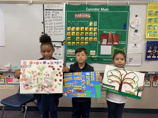 Students showing their 100th Day of School Projects.
